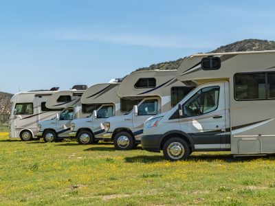 Different sizes of RVs in a line-up from smaller Class C, bigger Class C to a Class A motorhome in an outdoor setting